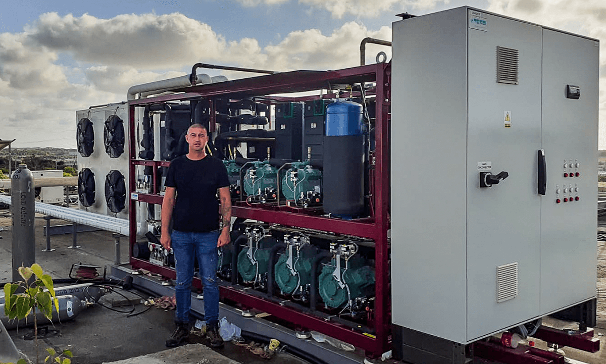 Nikolay Vodolzov of NIK Systems, with TEKO transcritical CO2 system atop roof of Israeli meat producer Mania Group's warehouse.